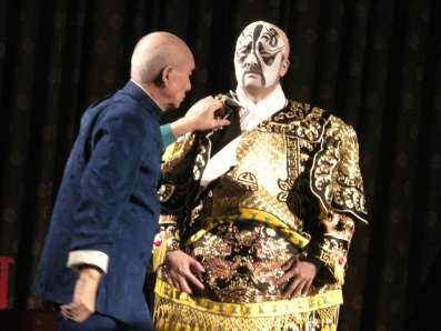 A performer being dressed for the Beijing Opera