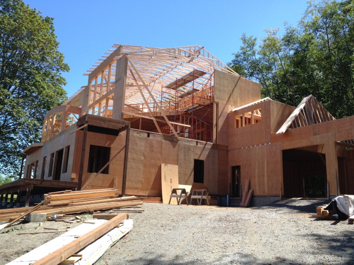Roof trusses are in place on the main part of the house, along with first- and second-floor decks.