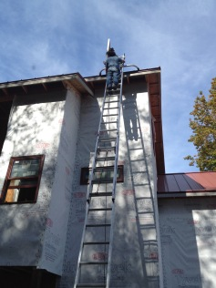 Worker up on ladder installing solar panels