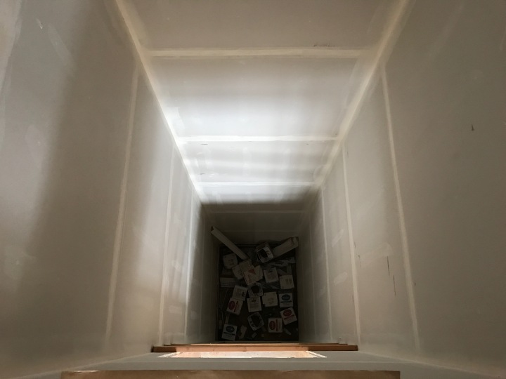 Looking down the elevator shaft, with empty drywall-tape boxes at the bottom